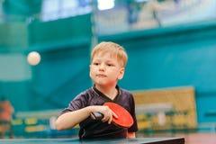Tischtennisspiel, Junge, der Tennisball in der Tennishalle spielt stockfoto