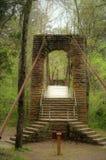 Tishomingo State Park Swinging Bridge. Sturdy timeworn Tishomingo stone and wood swinging bridge sits among greenery in dense forest Stock Photo