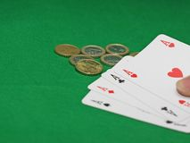 Tisonnier des as avec d'euro pièces de monnaie sur la table de casino Photographie stock libre de droits