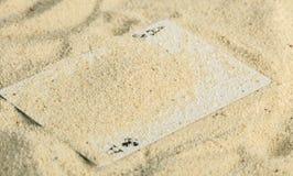 Tisonnier jouant des cartes enterrées dans une dune de sable image libre de droits