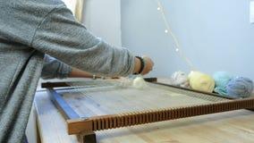 Tissage sur un cadre de métier à tisser La main du ` s de femme de plan rapproché met le fil dans le cadre pour le tissage Vue de clips vidéos