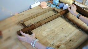 Tissage sur un cadre de métier à tisser Le ` s de femme de plan rapproché remet préparer le cadre de métier à tisser au tissage banque de vidéos