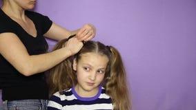 Tissez les petits tresses mignons d'une fille Le coiffeur fait une coiffure de fille banque de vidéos