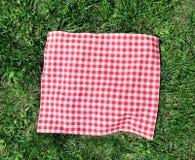 Tissu à carreaux rouge sur la vue supérieure d'herbe verte photographie stock libre de droits