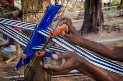 Tissu blanc et bleu traditionnel pour l'habillement étant extérieur tissé sur métiers à main en Côte d'Ivoire, Afrique de l'ouest photographie stock libre de droits