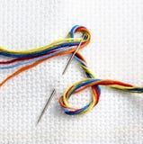 Tissu blanc pour la broderie et aiguille avec coloré Image stock