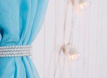 Tissu bleu sur un fond en bois blanc au foyer sélectif Le rideau est décoré des perles blanches À l'arrière-plan, électrique Photo stock