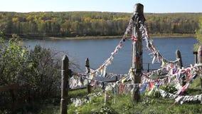 Tissu coloré païen pour des spiritueux sur la falaise au-dessus de la rivière banque de vidéos