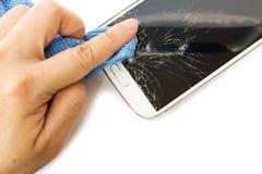 Tissu d'utilisation de la main de la femme nettoyant un téléphone intelligent blanc cassé Image libre de droits
