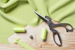 Tissu de chaux de coupe avec des ciseaux d'un Taylor sur la table en bois Photos libres de droits