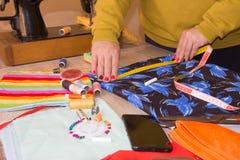 Tissu de ciseaux du ` s de tailleur de tailleur d'entaille de Hands de tailleur Tailleur de femme travaillant à une boutique de t photo libre de droits