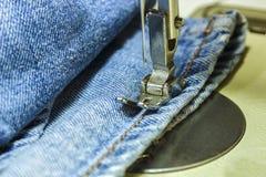 Tissu de denim sur la machine à coudre Plan rapproché du proce de couture Photographie stock