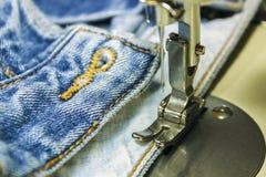 Tissu de denim sur la machine à coudre Plan rapproché du proce de couture Images libres de droits