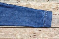 Tissu de Jean sur le fond en bois Photo libre de droits