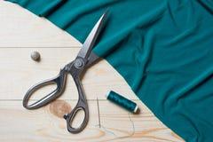 Tissu de turquoise de coupe avec des ciseaux d'un Taylor sur la table en bois Image libre de droits