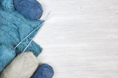 Tissu et écheveaux tricotés de laine sur la table en bois Images stock