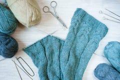 Tissu et écheveaux tricotés de laine sur la table en bois Photo stock