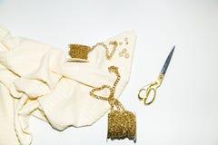 Tissu et accessoires blancs pour l'ouvrière couturière, la chaîne d'or et les ciseaux d'or images libres de droits