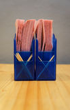 Tissu et cure-dents roses en boîte bleue, table en bois et ciment b photographie stock libre de droits
