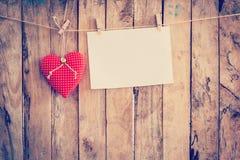 Tissu et pose de papier peint de coeur sur la corde à linge au fond en bois Photo libre de droits