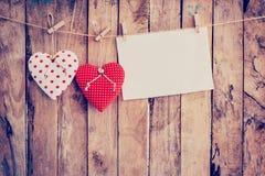 Tissu et pose de papier peint de deux coeurs sur la corde à linge au backgr en bois Photographie stock