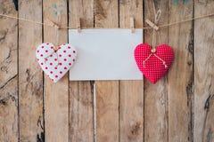 Tissu et pose de papier peint de deux coeurs sur la corde à linge au backgr en bois Photos libres de droits