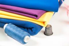 Tissu, fil, dé et centimètre colorés Photographie stock libre de droits