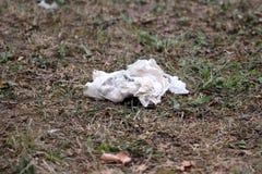 Tissu froissé de livre blanc jeté en nature comme déchets entourés avec l'herbe brune verte et sèche au coucher du soleil image stock