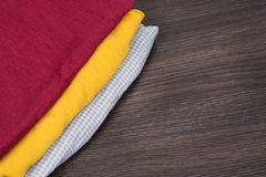 Tissu jaune et rouge une pile de vêtements, et de textiles Échantillons de tissu de couleur dans le magasin Tissu à carreaux gris photos stock