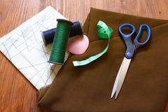 Tissu, mètre vestimentaire, ciseaux, craie, fils, modèles, plans photos stock
