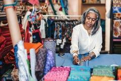 Tissu mûr d'inscription de femme dans sa boutique de tissu avant la coupure images stock