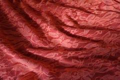 Tissu orange rosâtre plié de guipure avec des ombres Photos libres de droits