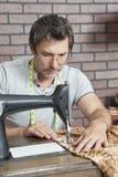 Tissu piquant de couturière masculine mûre sur la machine à coudre Image stock
