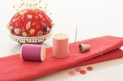 Tissu rouge, fil et d'autres outils de couture. Images libres de droits