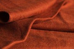 Tissu soyeux orange-foncé plié d'écharpe Photographie stock libre de droits