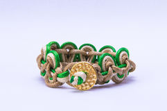Tissue bracelet with golden medal with green and brown colour. Close up of handmade bangle in tissue Stock Image