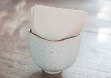 Tissue paper in ceramic cup on wooden table Stock Photos