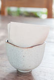 Tissue paper in ceramic cup on wooden table Stock Photography