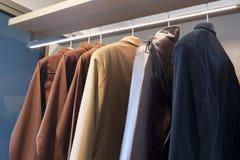 Tissus accrochant dans la garde-robe en bois à la maison photographie stock libre de droits
