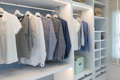 Tissus accrochant dans la garde-robe en bois à la maison images stock