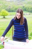 Tissus accrochants de jeune fille sur la corde à linge photo stock