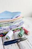 Tissus, ciseaux et fil de pile sur la table blanche Image libre de droits