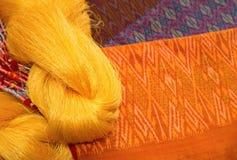 Tissus en soie thaïlandais et fils en soie crus matériels Image stock