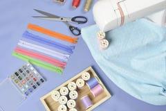 Tissus sur la machine à coudre parmi les ciseaux, boutons de chemise, zipp Photos stock