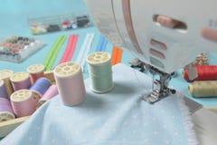 Tissus sur la machine à coudre parmi les ciseaux, boutons de chemise, zipp Photo stock