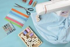 Tissus sur la machine à coudre parmi les ciseaux, boutons de chemise, zipp Images stock