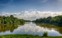 Tisza River in Tiszadob, Hungary. Cloudy blue sky. Green forest along the water. Summer scene.  royalty free stock photos
