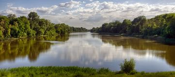 Tisza River in Tiszadob, Hungary. Cloudy blue sky. Green forest along the water. Summer scene.  royalty free stock image