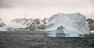 Titanic Iceberg. A titanic iceberg run aground in a South Georgia bay, backed by mountains stock photos