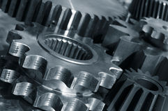 Titanium gears in action. Large gear machinery against solid titanium and in a metal blue toning concept, dark duplex idea Royalty Free Stock Photo
